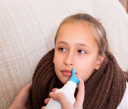 careful: Careful mom helping small girl using aqua del mar spray indoor