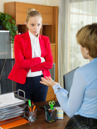 collegue: Young businesswoman having serious conversation with her collegue Stock Photo