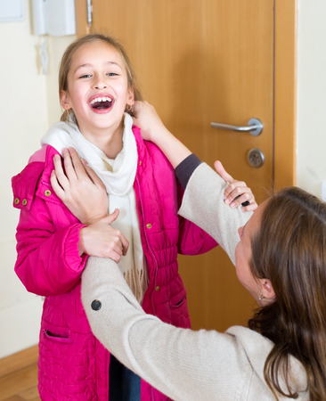wooly: Mother helps her little happy daughter to put on her warm overcoat and wooly scarf Stock Photo