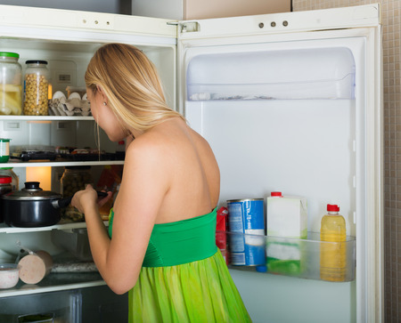 refrigerator kitchen: girl near opened refrigerator in kitchen at home