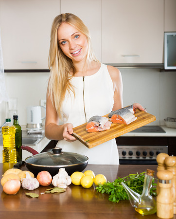 fryingpan: Smiling housewife cooking from salmon at home kitchen