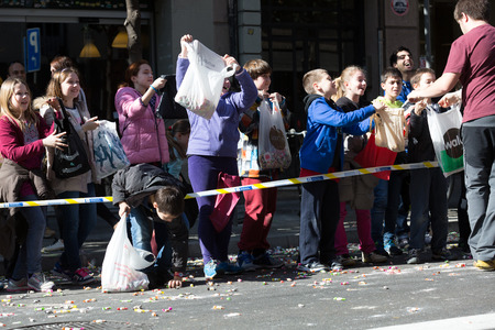 tons: BARCELONA, SPAIN - MARCH 3, 2015: Children  on  sidewalk waiting for caramels. Sant Medir festa - fiesta, during which participants were given tons of caramels