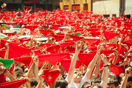 navarra: PAMPLONA, SPAIN - JULY 6: Cheering crowd of people with red shawl in square in July 6, 2013 in Pamplona, Spain. Opening of San Fermin Festival Editorial