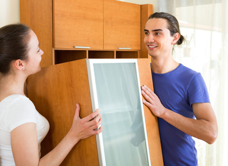 Happy smiling young family moving furniture in room together