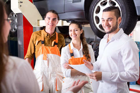 job satisfaction: Happy client and mechanics standing near a jacked up car in a car shop talking and smiling
