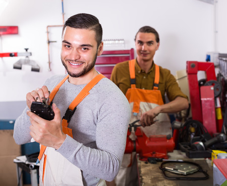 toiling: Two cheerful positive repairman toiling in locksmiths workshop and smiling