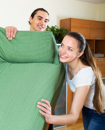 Young family doing relocation of furniture at living room