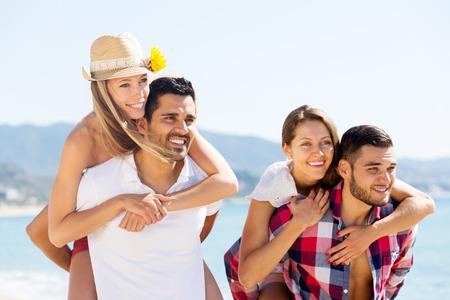 romance: smiling couples hugging on beach enjoying romance and sun. Focus on the left couple
