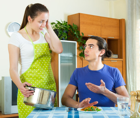 insipid: Unhappy woman serving lunch her man at table