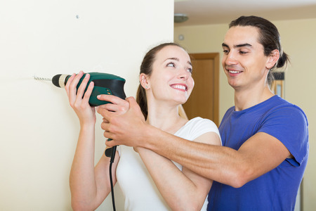 modifying: Young happy couple drilling wall with drill at home Stock Photo