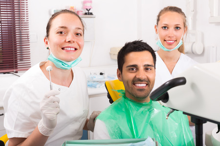 contented: Smiling female dentist with assistant and contented patient at dental clinic