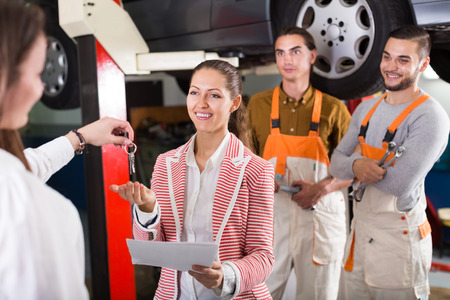 renewal: Insurance agent discussing with mechanics renewal of the car