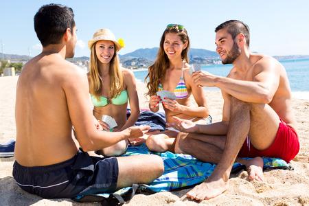 Amigos descansando en una playa que se sienta en la toalla y jugar juego de cartas de póquer
