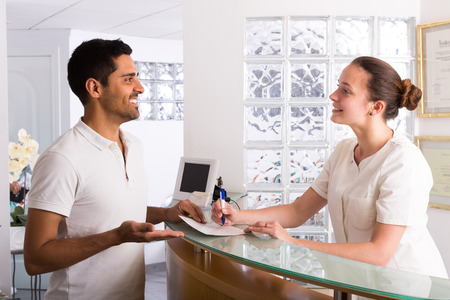 receptionists: Smiling guy in the waiting room of the hospital