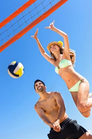 balon de voley: Joven pareja de voleibol de juego sonriente en la playa de la luna de miel