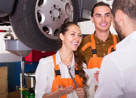 renewal: Smiling man client satisfied with mechanics renewal result indoor