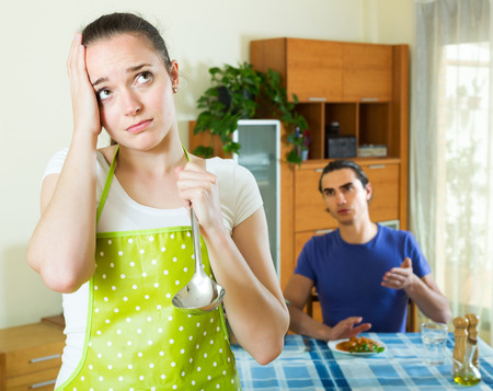 fetid: Unhappy young girl serving lunch her man at table Stock Photo