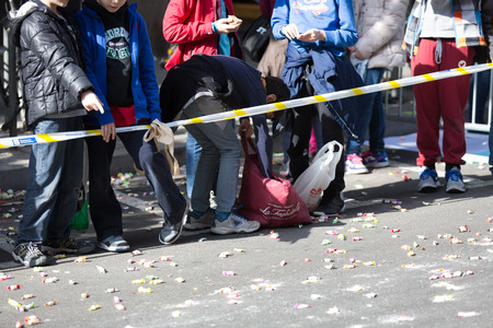 tons: BARCELONA, SPAIN - MARCH 3, 2015: Children  on  sidewalk waiting for caramels. Sant Medir festa - event, during which participants were given tons of caramels Editorial