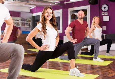 adult learners: Entrenador de la aptitud que muestra a jóvenes estudiantes nuevos ejercicios en clase Foto de archivo