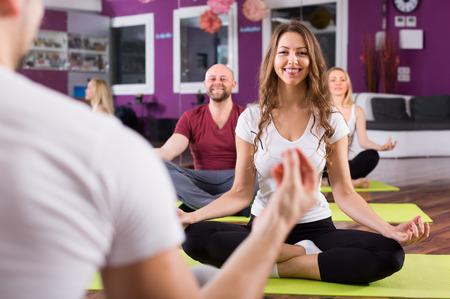 estudiantes adultos: Entrenador mostrando a adulto Estudiantes nueva postura de yoga en la sala de