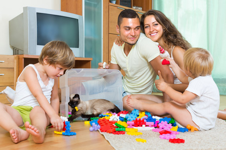 erector: Joyful parents and two little daughters playing with plastic toys in home