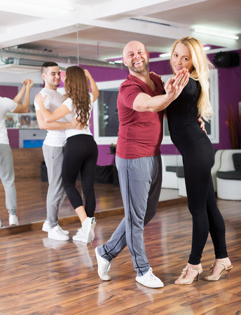 ballroom dancing: Cheerful couples enjoying of partner dance and smiling indoor