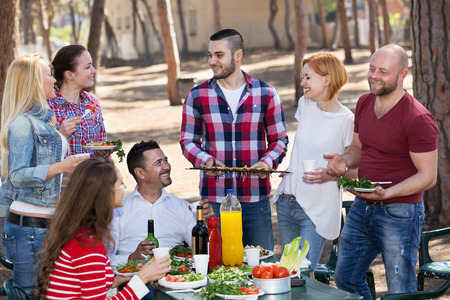 recollections: Cheerful happy friends posing and taking a pictures together at barbecue Stock Photo