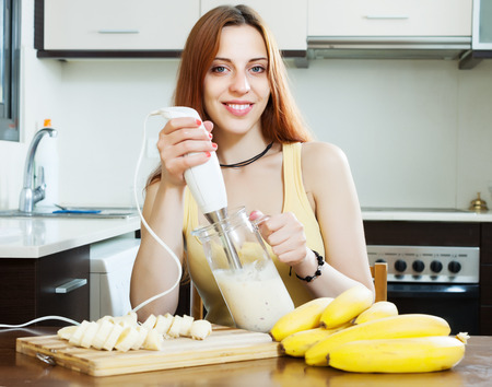 banana: Positive woman making beverages with blender from bananas and milk at domestic kitchen