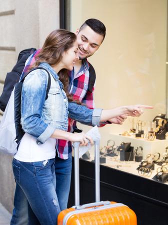 shopwindow: portrait young couple of tourists choosing wristwatch at shopwindow Stock Photo