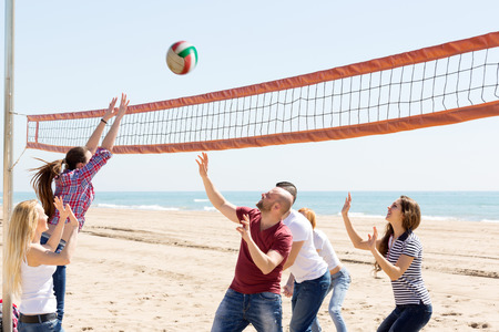 freetime activity: Group of friends having fun at beach and playing ball .Focus on the right pair