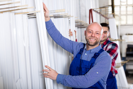 toolroom: Professional industry workers are choosing white PVC window profiles inside a warehouse