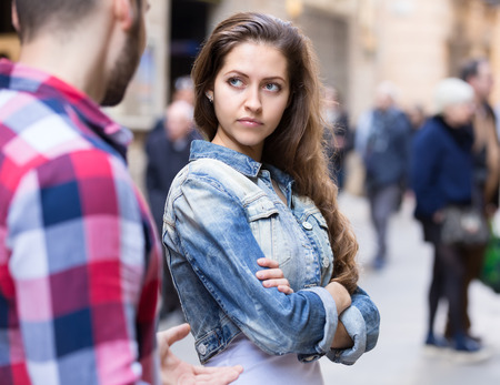 conflicto: Pares que tienen una pelea en una calle de la ciudad. La mujer est� de pie media volvi� a su novio con una mirada decepcionada en su hermoso rostro