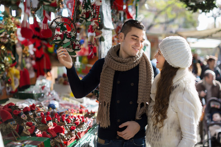festal: Happy  girl with boyfriend choosing Christmas decoration at Barcelona. Selective focus Stock Photo