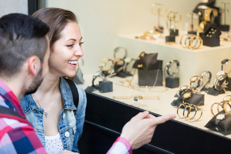 shopwindow: Young adults looking at shopwindows with luxury bracelets, jewelry and watches