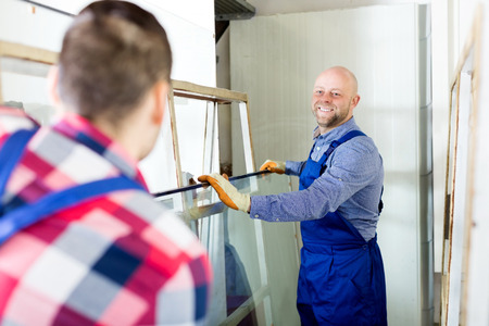 glasswear: Adult workers working with glass for windows at workshop Stock Photo
