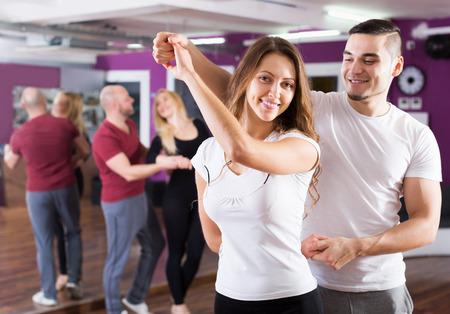Happy adult couples enjoying of partner dance indoor