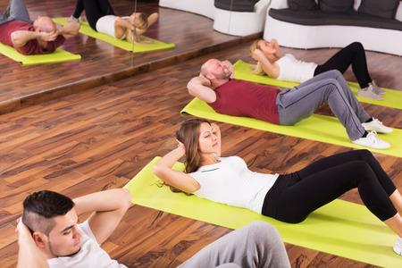 estudiantes adultos: Entrenador joven de la aptitud que muestra a adulto Estudiantes de nuevo ejercicio en la clase