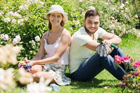 floriculturist: Young smiling family with gardening tool in their backyard garden