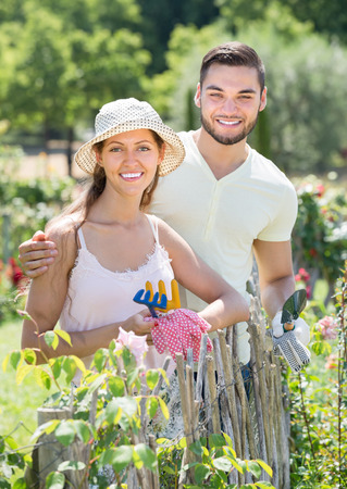 floriculturist: Young family in gloves planting flowers in garden Stock Photo