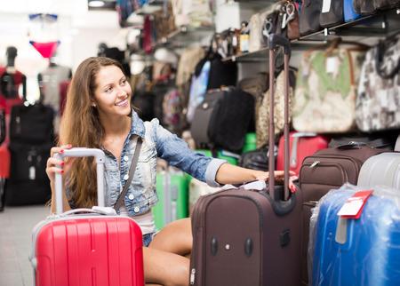 portmanteau: adult european  woman choosing luggage bag in shop Stock Photo