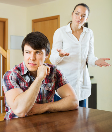grievance: Young married couple having serious quarrel at home interior