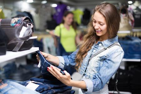 Smiling girl shopper choosing new jeans at store