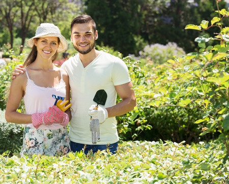 floriculturist: Smiling couple is engaged in gardening together