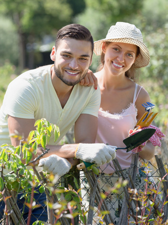 Happy family in gloves with horticultural sundry in garden