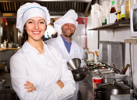 comercial: Feliz chef y cocinero que trabaja en la cocina del restaurante