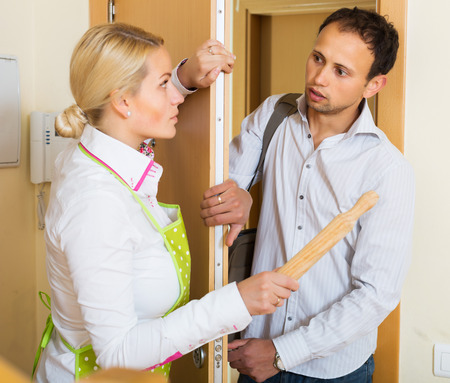 rollingpin: Angry serious girl threatens with rolling-pin for a frightened man
