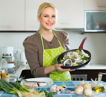 cook griddle: Smiling  housewife  cooking fish with lemon at home kitchen