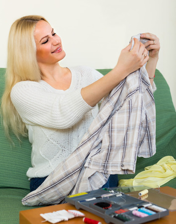 mending: Attentive european girl on couch mending linen and smiling
