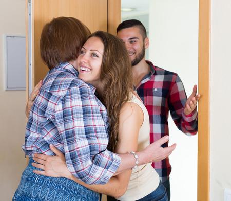 personas saludandose: Reunión mayor de la mujer joven pareja en la puerta