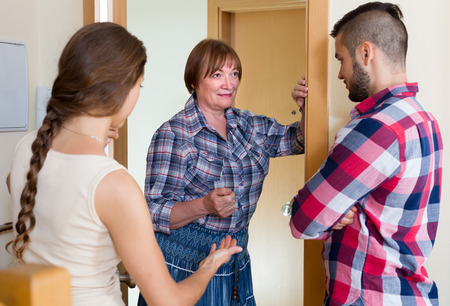threatens: Disappointed senior woman threatens their young neighbors at the door